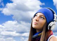 девушка в наушниках смотрит на небо