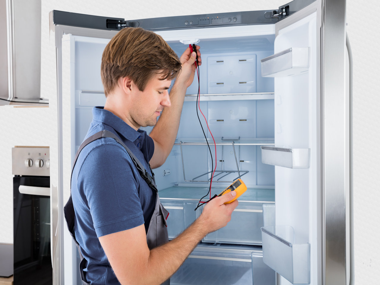 мастер смотрит на прибор, который покажет, что с холодильником