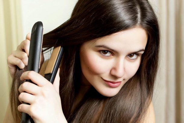 девушка держит выпрямитель для волос