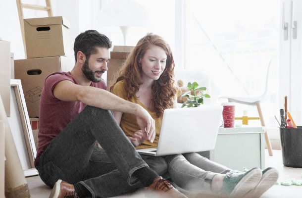 девушка и ее парень в новом доме сидят с ноутбуком