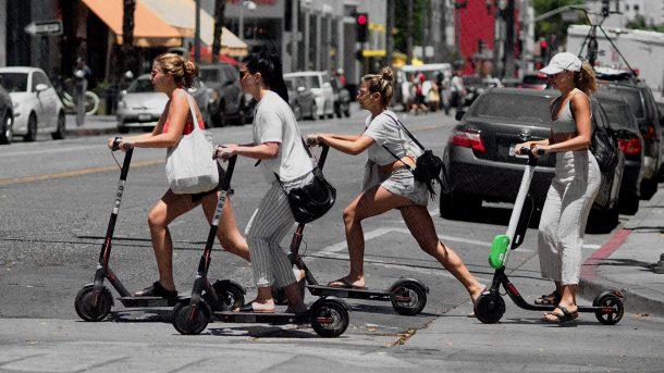 женщины на электросамокатах-переезжают пешеходный переход