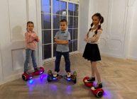 дети стоят на гироскутерах в доме