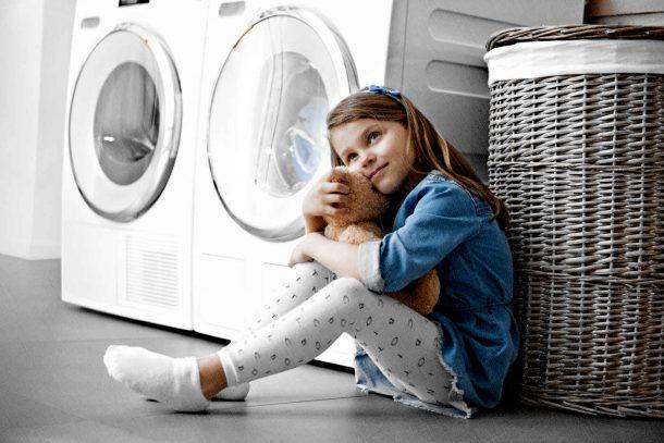 стиральная машина и ребенок с вещами рядом