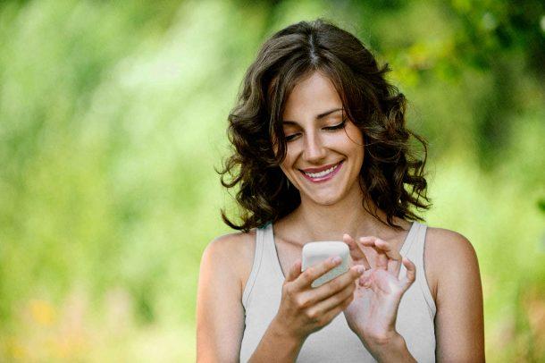 девушка радуется общению на телефоне