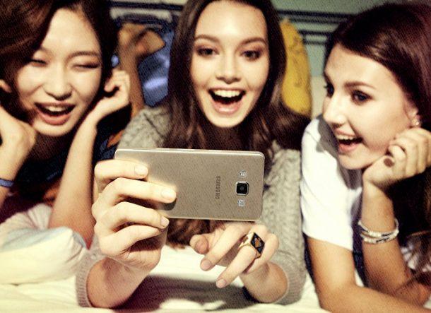 девушка с подружками смеется и показывает фото в телефоне самсунг