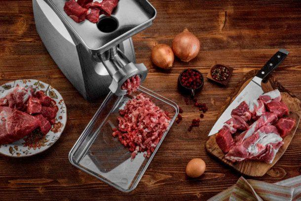 мясорубка на столе с мясом и фаршем