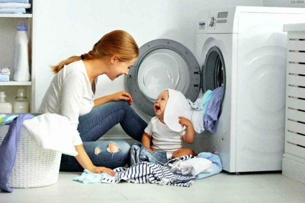 смех ребенка и мамы около постиравшей белье стиральной машинки
