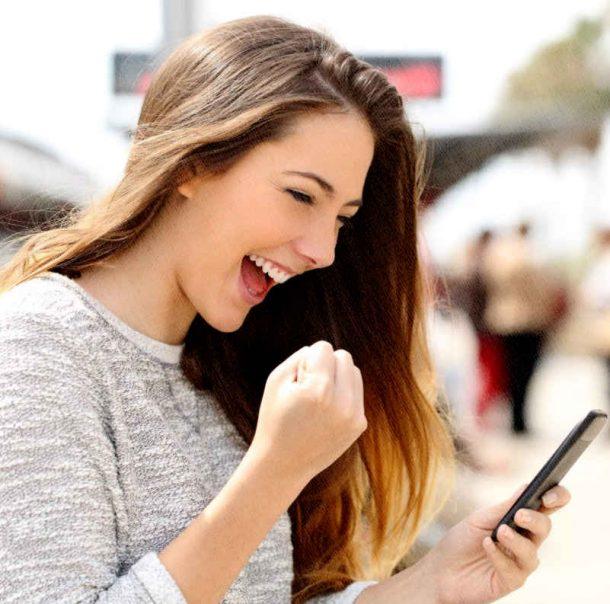 девушка радуется, что купила потрясающий смартфон, который не глючит
