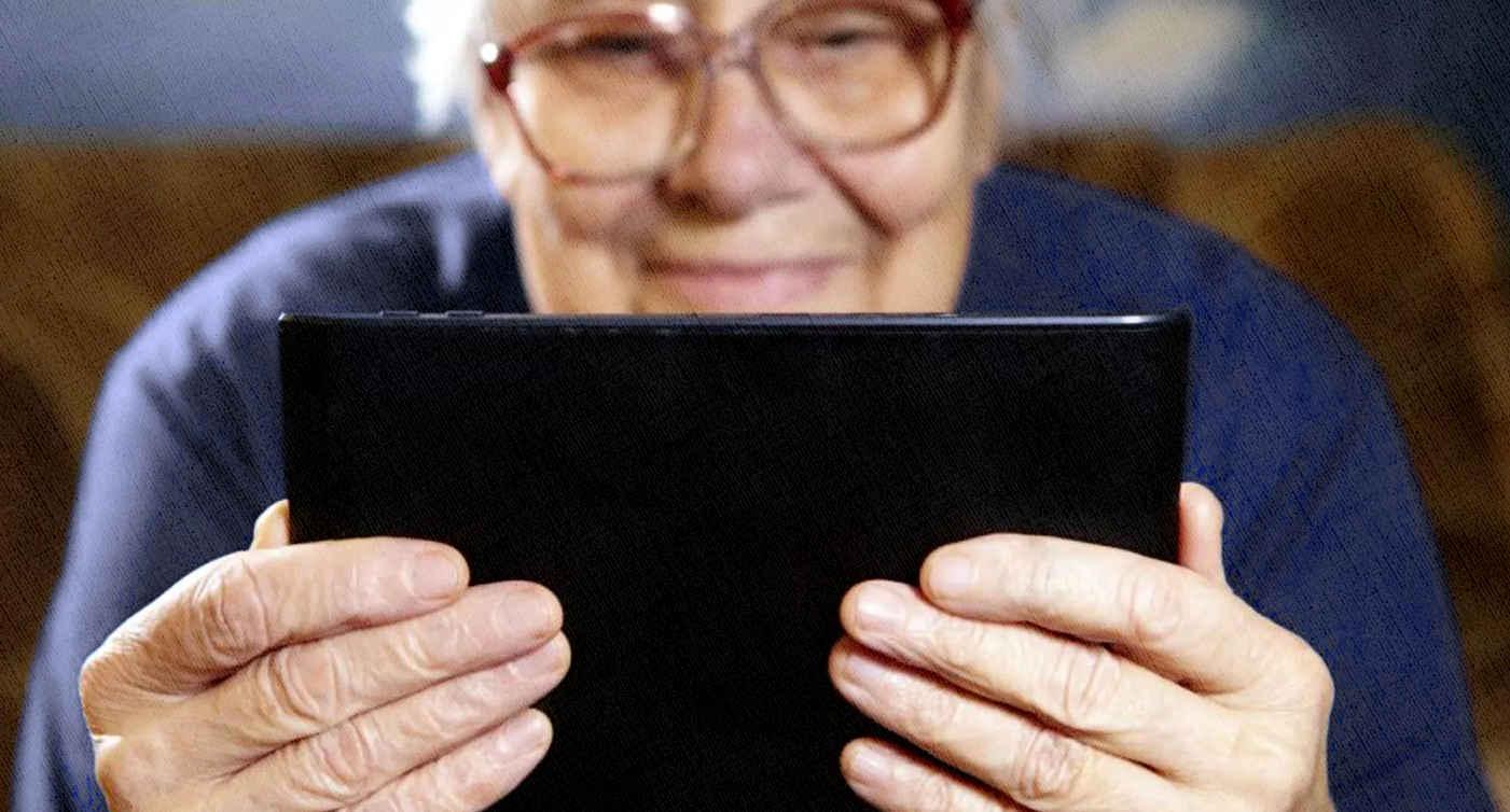 бабушка смотрит видео по планшету и общается по вацапу с родственниками