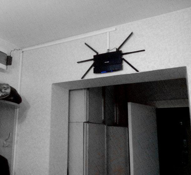роутер в виде паука весит над потолком в комнате