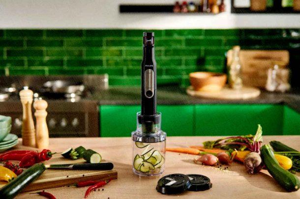 блендер стоит на кухне среди овощей и фруктов и работает