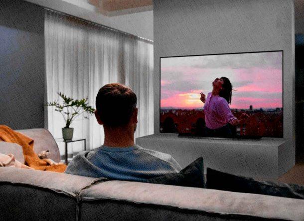 девушка и ее муж смотрят телевизор в гостиной