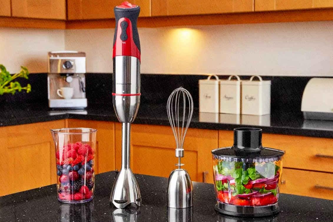погружной блендер на кухне с чашей полной ягод и овощей