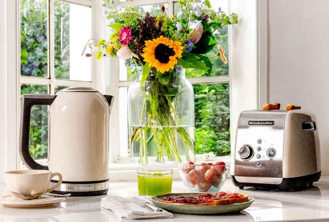 китчен чайник и тостерница стоят на столе с вазой и цветами около окна