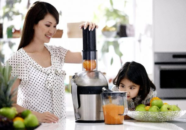 мама и девочка выжимают сок на соковыжималке лучшего качества