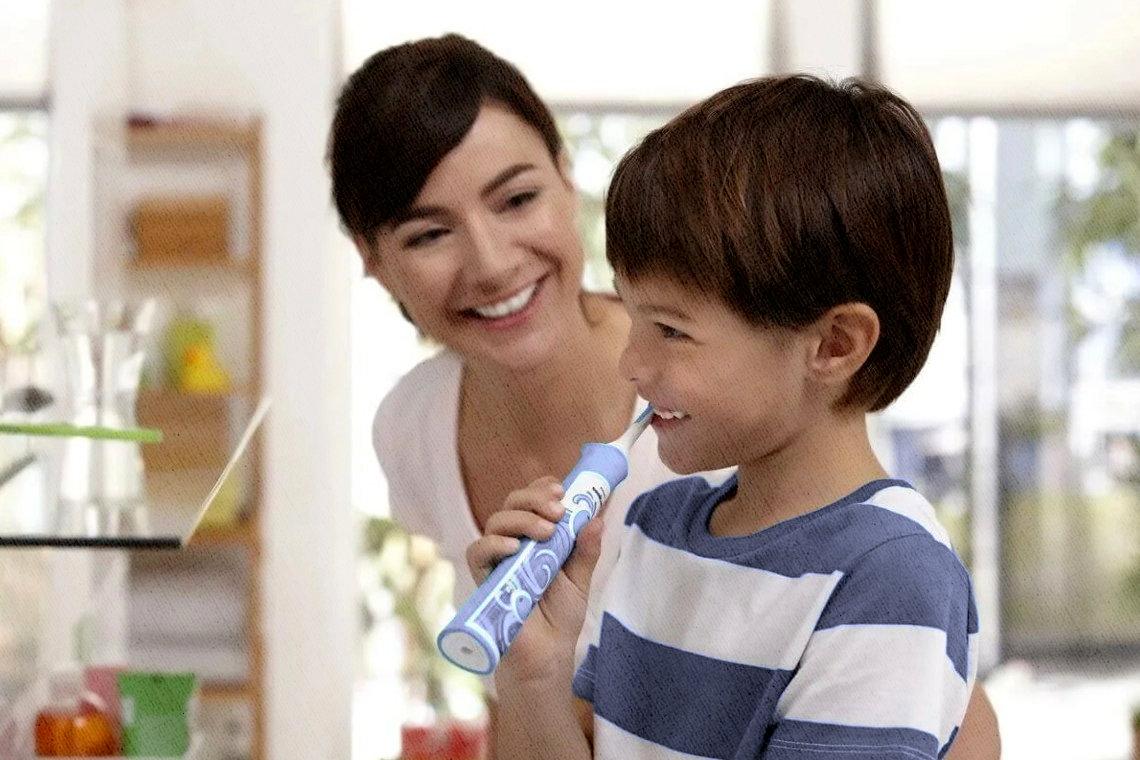 мама помогает мальчику справиться с чисткой зубов электрической зубной щеткой