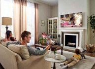 вся семья смотрит телевизор у себя дома и наслаждаются качеством картинки