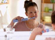 электрическая зубная щетка у девочки в руках перед зеркалом