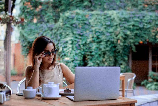 девушка сидит около ноутбука в кафе и работает над блогом в 2021 году