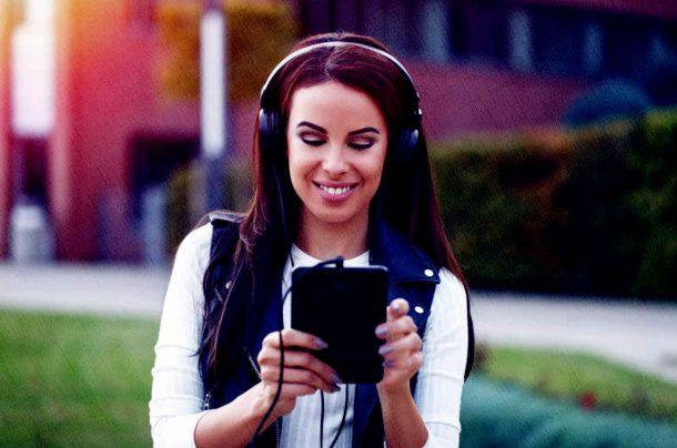 девушка смотрит в планшет 2021 года и слушает классную мелодию о жизни