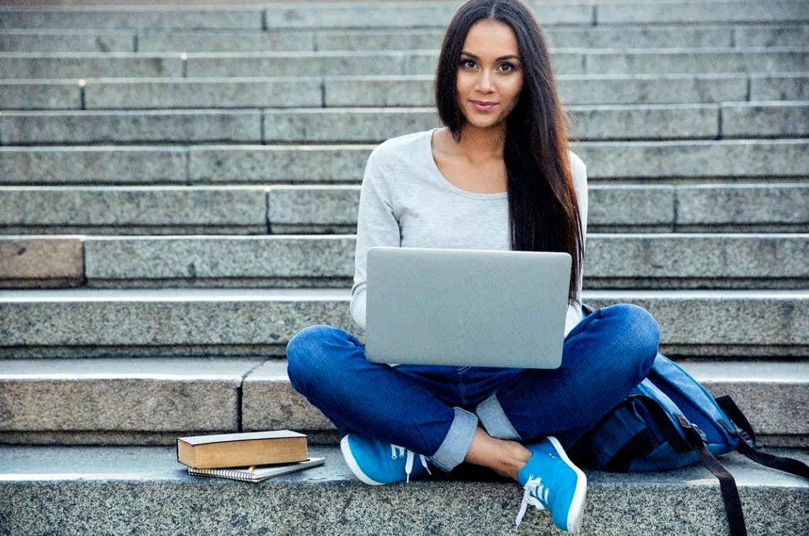девушка студентка сидит на ступеньках к универу и грызет гранит науки с помощью ноутбука