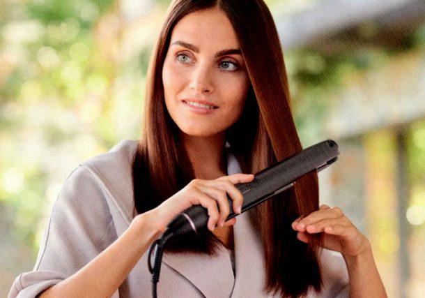 девушка выпрямляет волосы выпрямителем, ставшим лучшим в 2021 году
