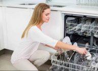 женщина берет из посудомоечной машины посуду чистую