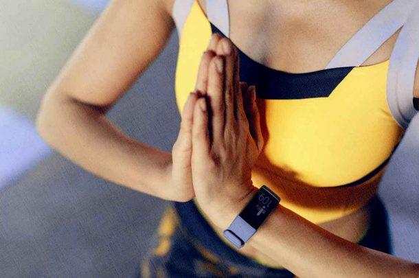 девушка гимнастка занимается с фитнес браслетом физическими упражнениями