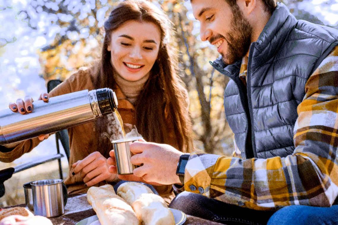 девушка наливает кипяток другу сидя на пикнике в лесу на солнце из термоса купленного по рекомендации Ростислава Кузьмина