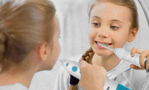 девочка пользуется ирригатором вымывая остатки пищи и зубной пасты а также улучшая микрофлору ротовой области