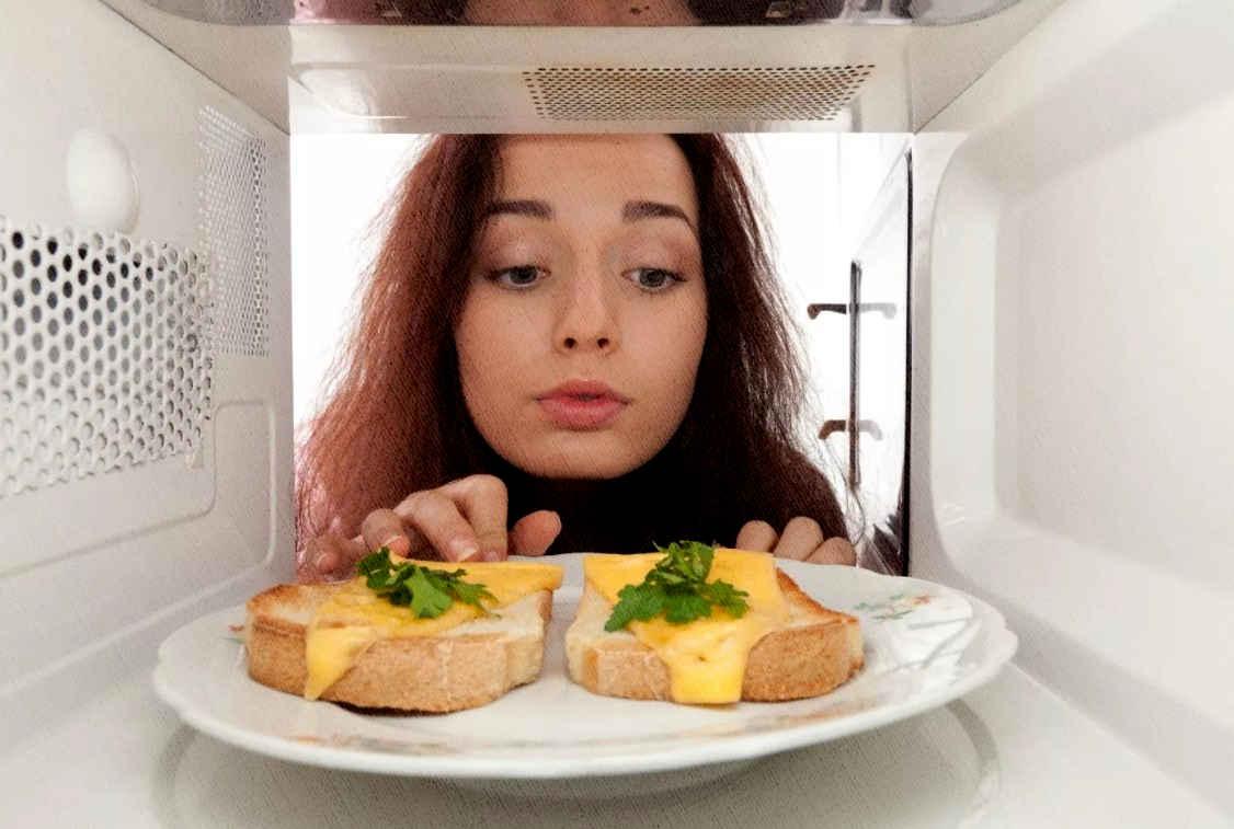 девушка заглядывает в микроволновку, дабы забрать бутерброды, которые приготовились