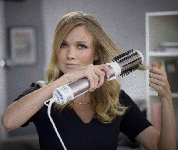 девушка пользуется фен щёткой для волос у себя дома перед зеркалом