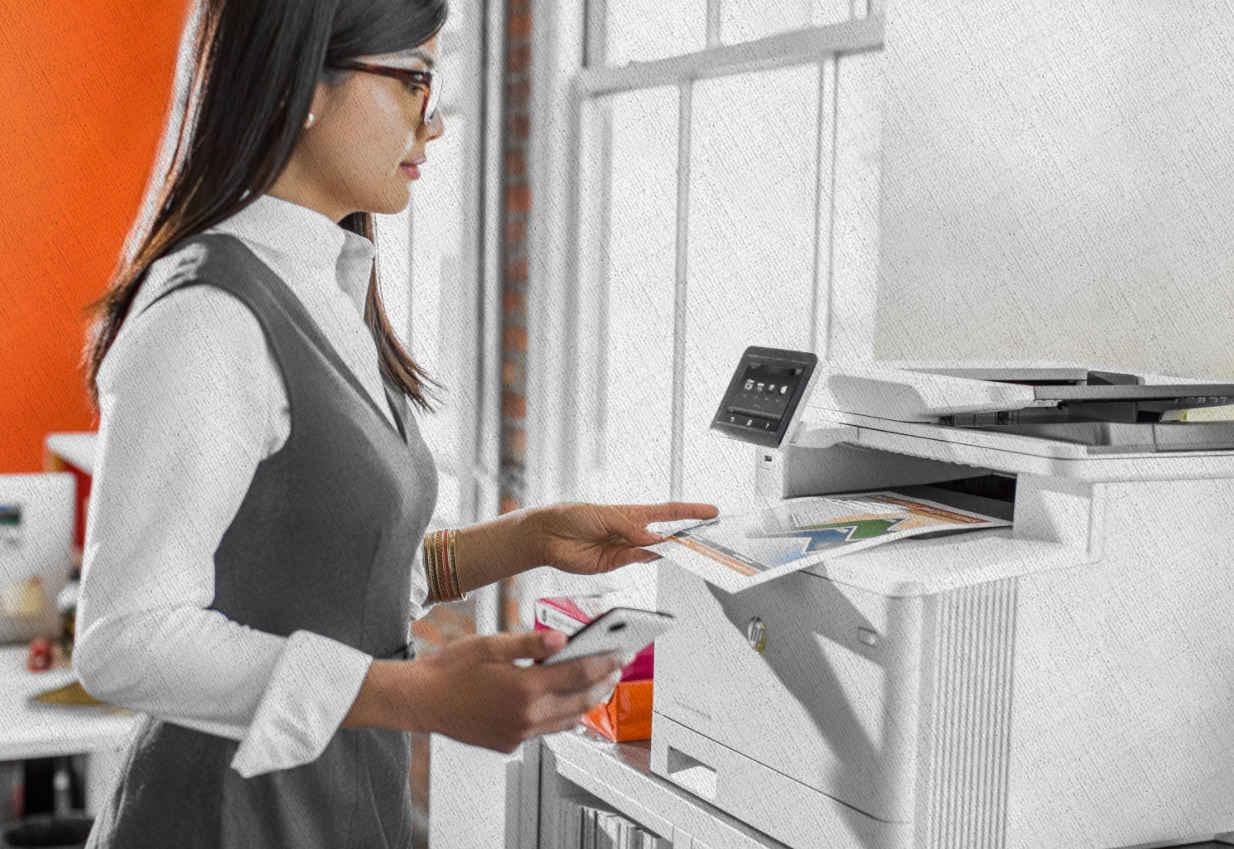 девушка распечатывает фото и графики в офисе через соединение мфу со смартфоном из рейтинга от Ростислава Кузьмина