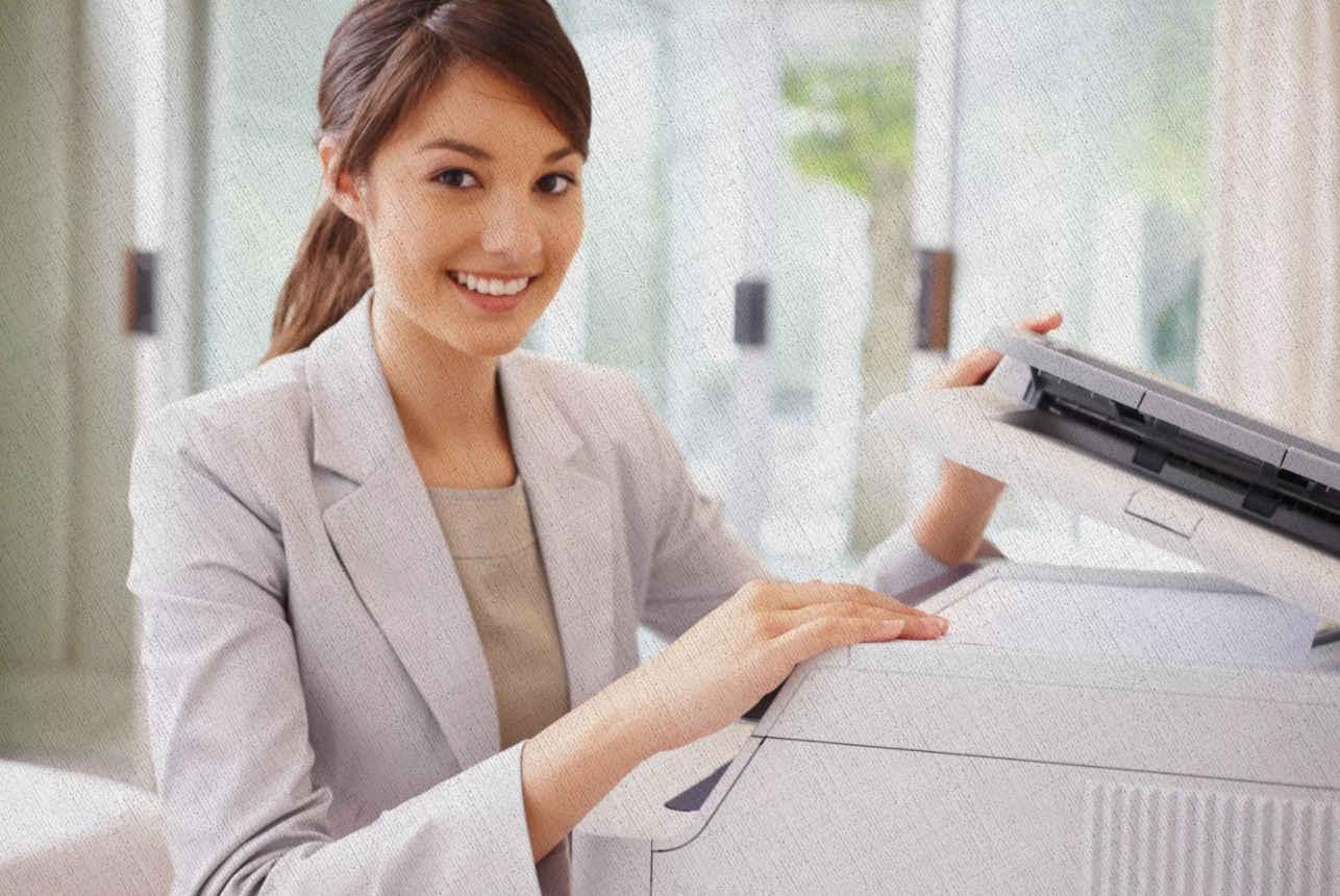 девушка загружает в принтер лазерный бумагу для печати
