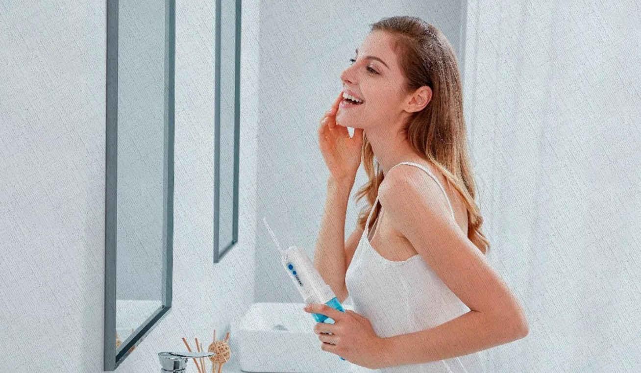 девушка радуется что у нее нет больше проблем с зубами так как она пользуется ирригатором из рейтинга 2021 года