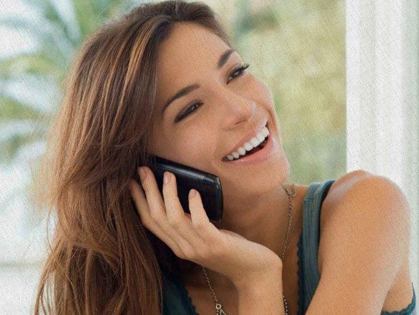 девушка разговаривает по смартфону с подружкой и счастлива так как купила его по рекомендации Ростислава Кузьмина