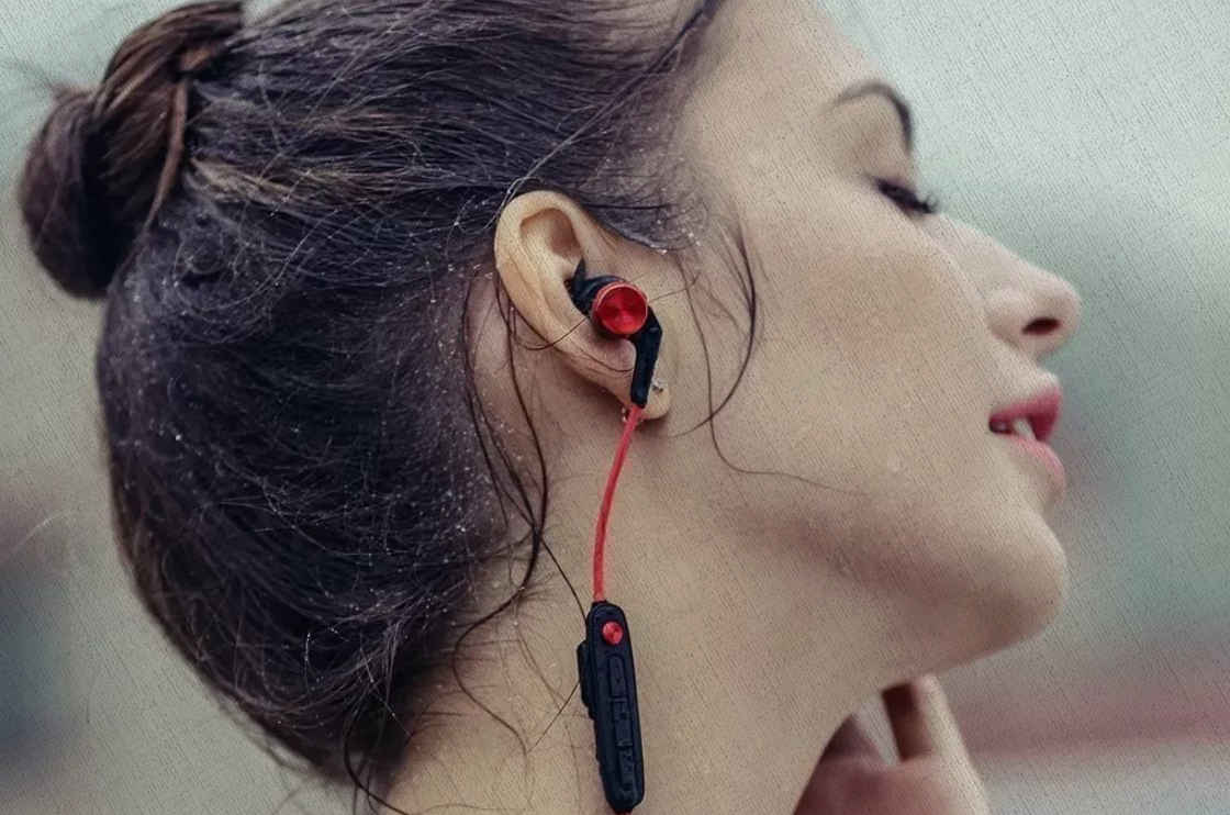 девушка слушает наушники из топа Ростислава Кузьмина беспроводных за 2021 год