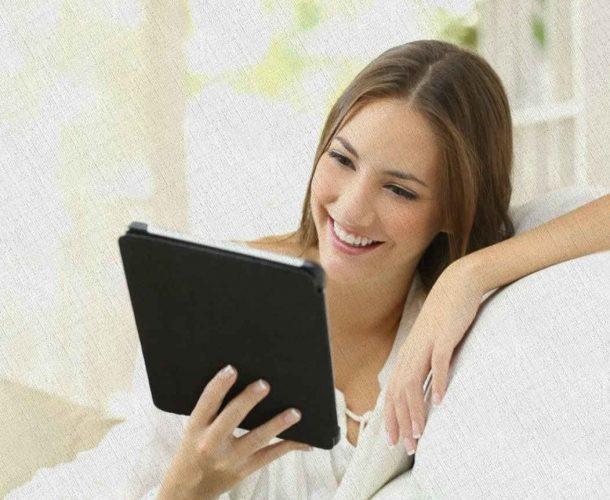девушка смеется в планшет разговаривая с родными и близкими