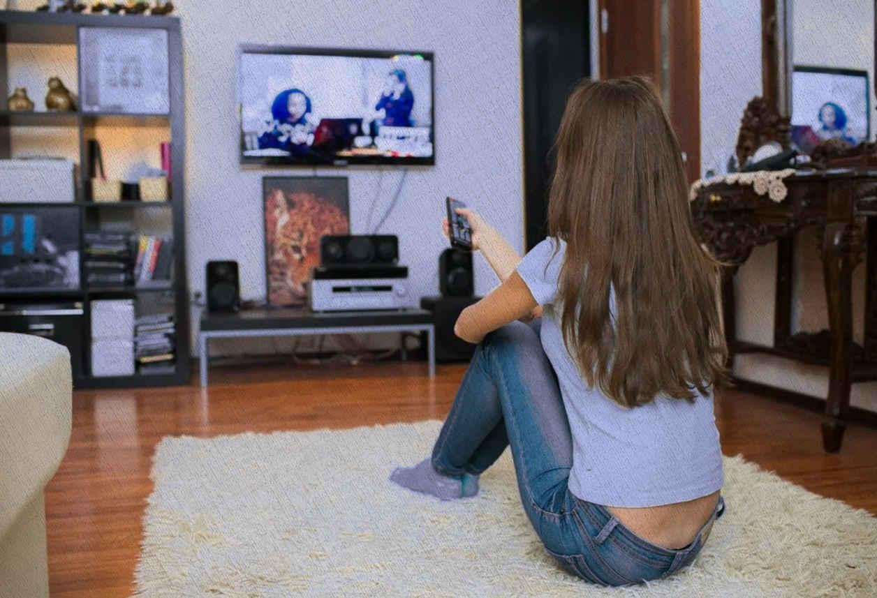 девушка смотрит телевизор, купленный по рекомендациям Ростислава Кузьмина
