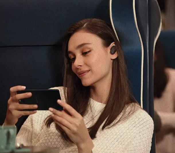 наушники беспроводные у девушки в ушах, купленные из рейтинга 2021 года, она смотрит фильм по телефону