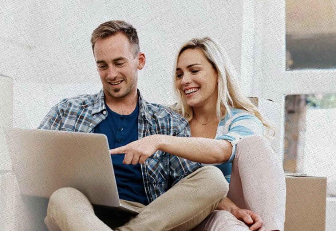 парень и девушка смотрят в экран ноутбука и смеются над ценами из рейтинга составленного не Ростиславом