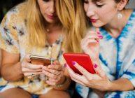 2 девушки выбирают через смартфоны новый телефон 2021 года на сайте Ростислава Кузьмина в рейтинге