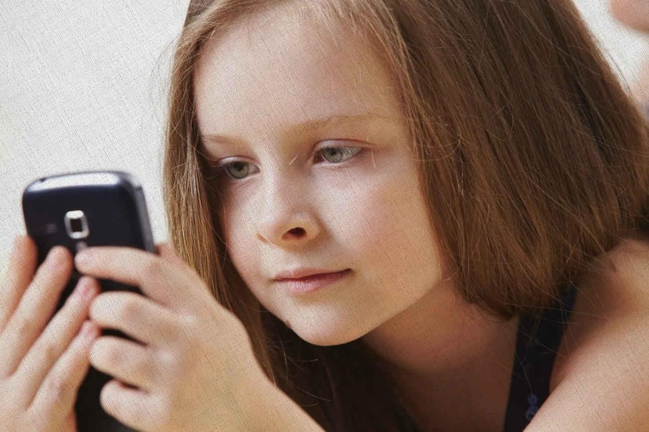 девочка читает про уроки на смартфоне 2021 года купленного по рекомендации Ростислава Кузьмина