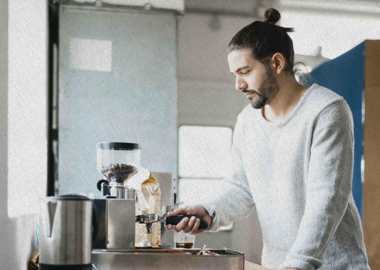 парень использует рожковую кофеварку у себя дома для приготовления кофе в 2021 году